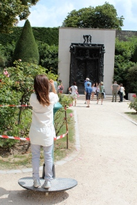 Child looks at Rodin's Gates of Hell with a telescope, bronze