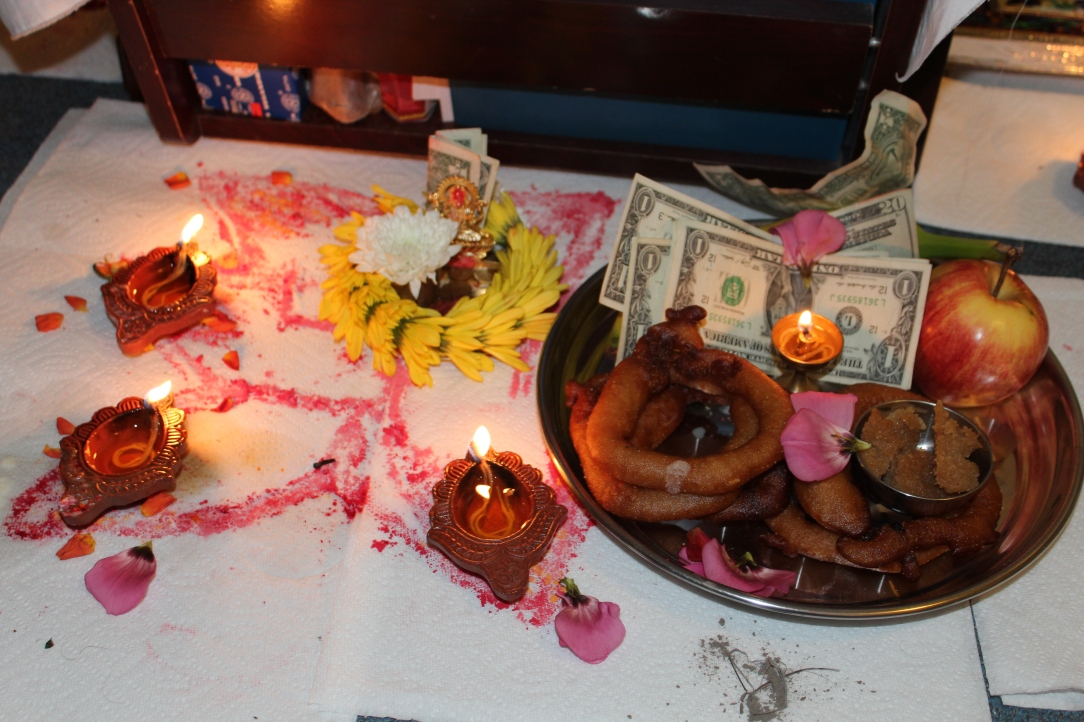 Sel roti sweet pastry, money, oil lamp. flower offerings at the Diwali altar