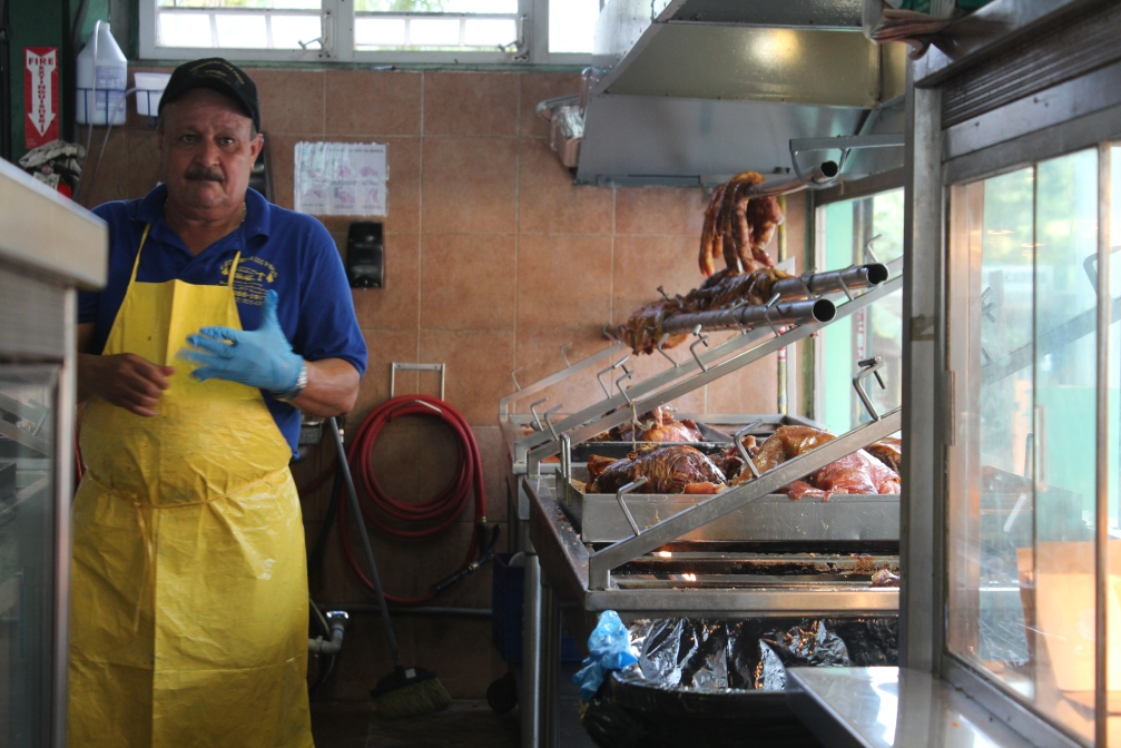 Hog butcher changes gloves, Lechonera Los Pinos, Guavate