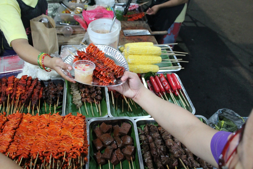 Isaw (barbecue) chicken intestine, pepper, onion and vinegar dipping sauce. Also pictured, center, Betamax (congealed pork's blood cubes). Banchetto, Manila, Philippines.
